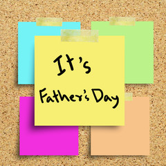 Sticky note with Happy Fathers Day on a cork bulletin board.