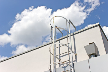 Safety metal ladder to the roof and  blue sky