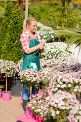 Garden center woman write notes potted flowers