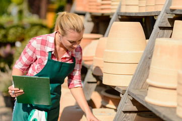 Garden center woman looking down clay pots