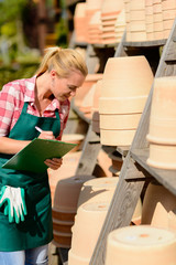 Garden center woman write notes clay pots
