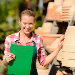 Garden center woman by clay pots shelf
