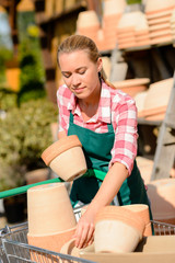 Garden center woman putting clay pots cart