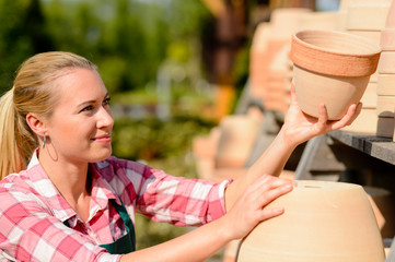 Garden center woman putting clay pots shelf