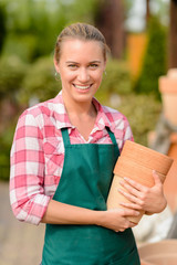 Smiling garden center woman holding clay pots
