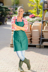 Garden center woman worker standing crossed arms