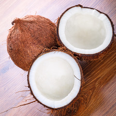 Coconut cut in half on wooden board