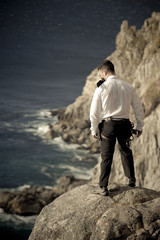 Young handsome guy standing on rock above ocean
