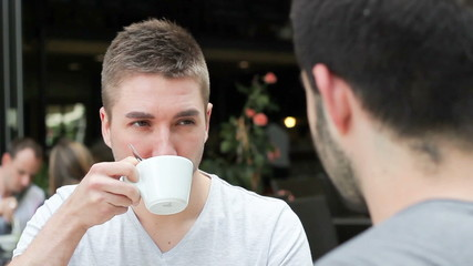 Young handsome caucasian man relaxing outside, drinking coffee