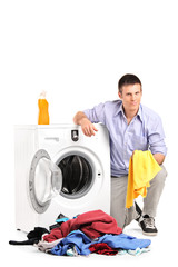 Young man emptying a washing machine