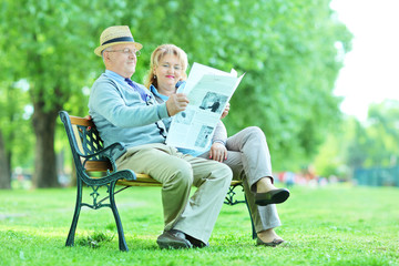 Mature couple reading a newspaper in park