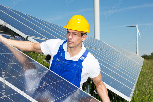 Photovoltaic engineer or installer installing solar panel - 65995811