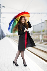 Woman with umbrella adjusts her hair