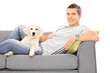 Happy man lying on couch with a puppy