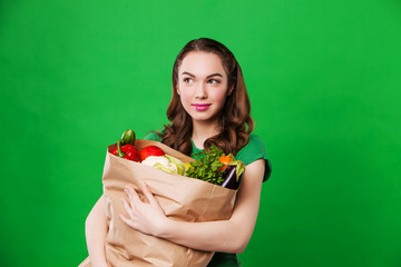 beautiful smiling woman holding a grocery bag full of fresh and