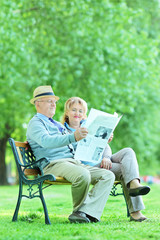 Elderly couple sitting in park and reading the news
