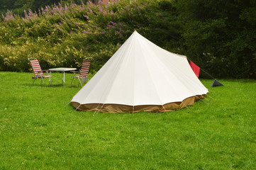 Campsite with a canvas tent and camp furniture on grass