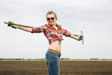 Woman with rake on cultivated field ground