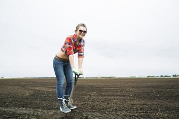 Woman standing on sharp shovel and smile