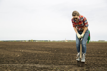 Woman standing on sharp shovel looking down