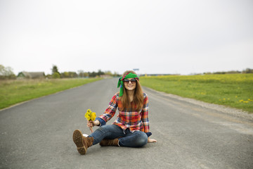Woman with yellow flowers on asphalt road