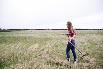 Woman rake dry grass on farm field