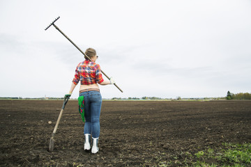 Woman with rake and shovel move away