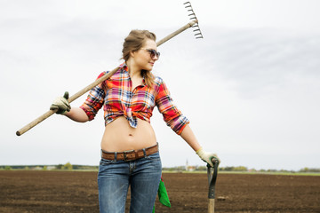 Woman with rake and shovel at shirt