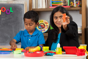 Hispanic Mom with Child in Home School Setting Showing Craft