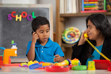 Mom and Child in Home School Setting Playing on the Phone