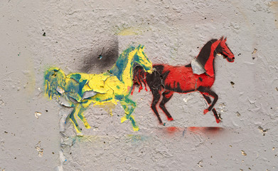 Graffiti of two horses peeling on concrete