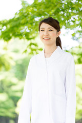 young asian doctor relaxing on green background
