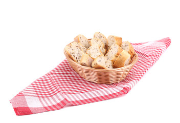 Wicker basket with bread slices on tablecloth.