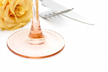 Place setting. Knife, fork, glass with yellow rose on white