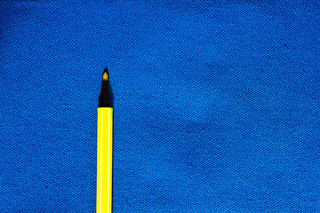 yellow color pen on Blue canvas fabric background