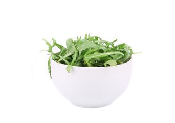 Fresh arugula in white bowl.