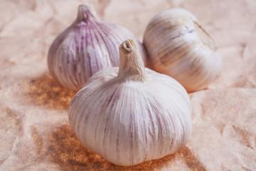 Three garlic on paper surface