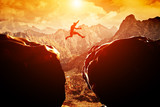 Fototapety Man jumping over precipice between two mountains at sunset