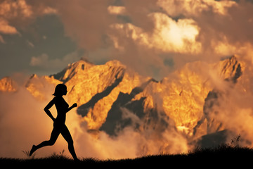 Silhouette of a woman running jogging in the mountains at sunset