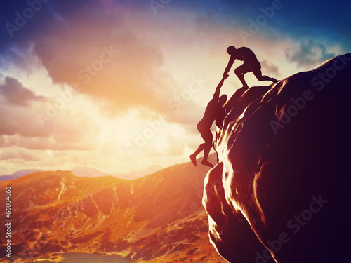 Leinwandbild Motiv Hikers climbing on mountain. Help, risk, support, assistance