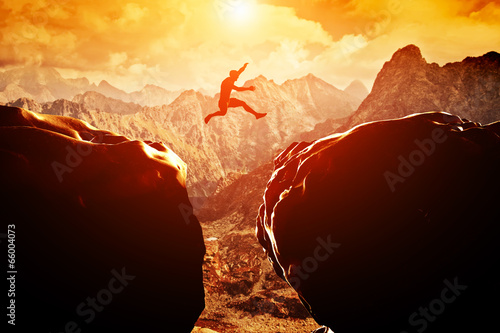 Leinwandbild Motiv Man jumping over precipice between two mountains at sunset