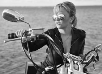 Black and white photo of young beautiful woman on bike
