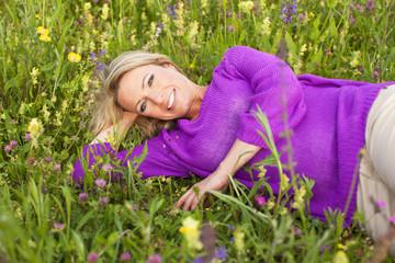 Hübsche blonde Frau liegt im Gras