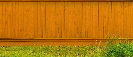 Background long blank wooden fence with grass in the countryside