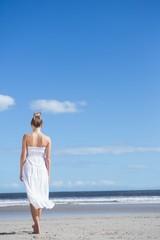 Blonde in white dress walking on the beach