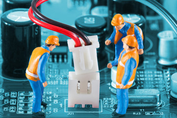 Miniature engineers fixing wire connector