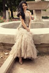 beautiful woman in luxurious dress sitting beside a fountain