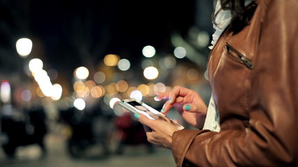 Woman watching photos on smartphone late at night in the city