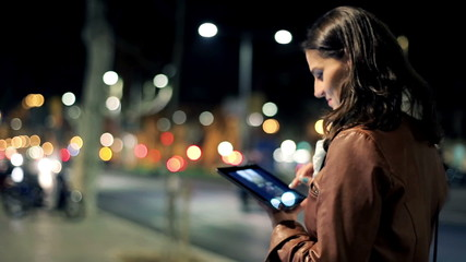 Woman watching photos on tablet late at night in the city