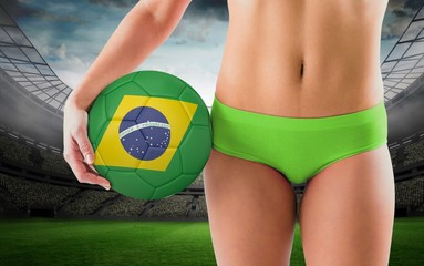 Composite image of fit girl in green bikini holding brazil footb